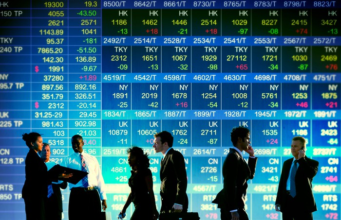 Men and women in suits, standing and walking in front of a display of stock prices.
