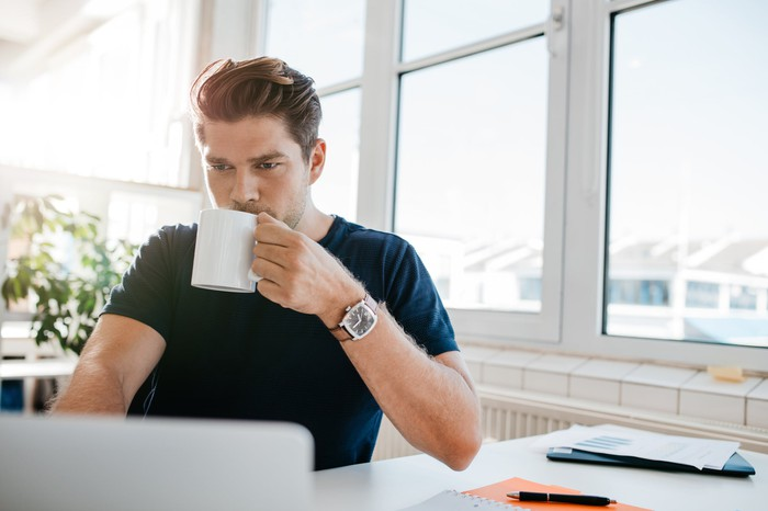 Young male adult at a laptop with mug in hand