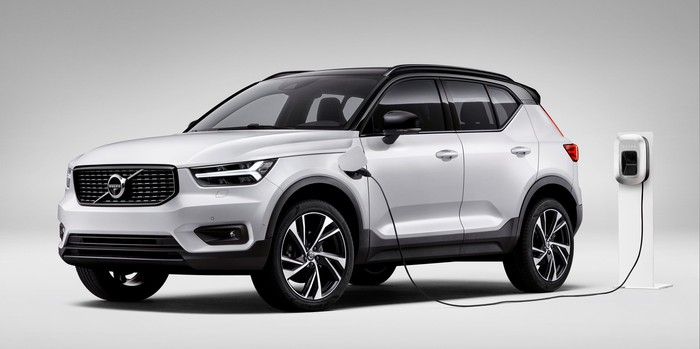 A white Volvo XC40 plug-in hybrid SUV, shown plugged into a charger.