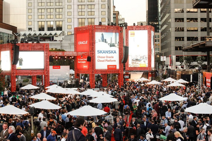 Large crowd in urban setting with elevated boards showing Oracle logo and promotional materials.