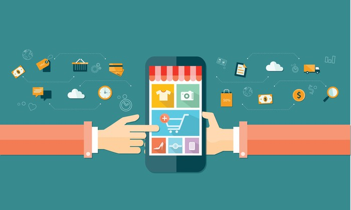 An illustration of a mobile shopping site on a smartphone. A hand is holding the phone, and another hand from the opposite side of the image is selecting items to purchase.