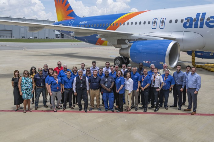 A group of employees pose in front of an Allegiant Air jet