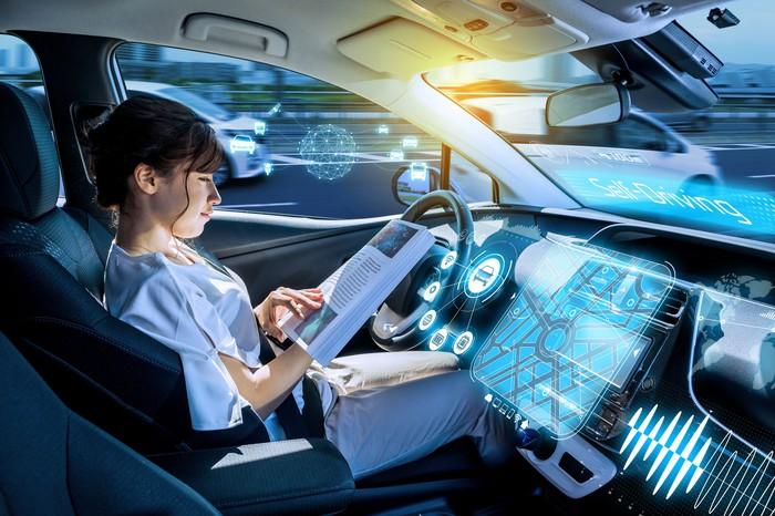 A woman sits in a driverless car, reading while behind the wheel in traffic.