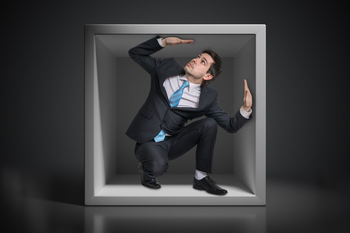 A man in a suit is trapped in a box.