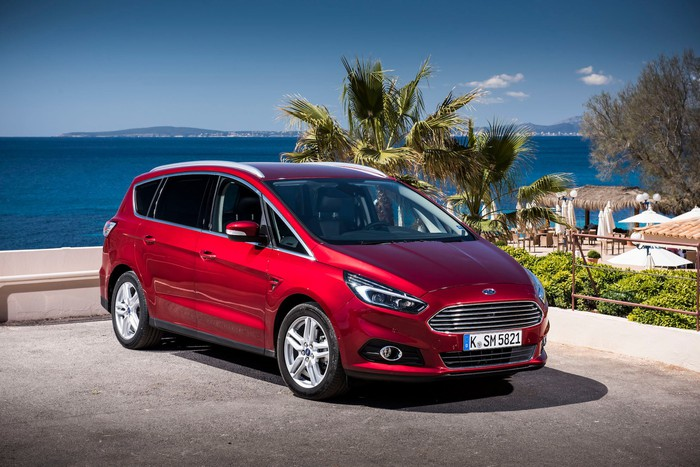 A red Ford S-Max, a tall five-passenger wagon, parked at an upscale beach.