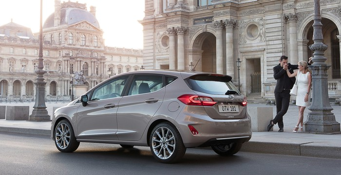 A taupe Ford Fiesta hatchback parked in a European city. A smartly-dressed couple is standing nearby.
