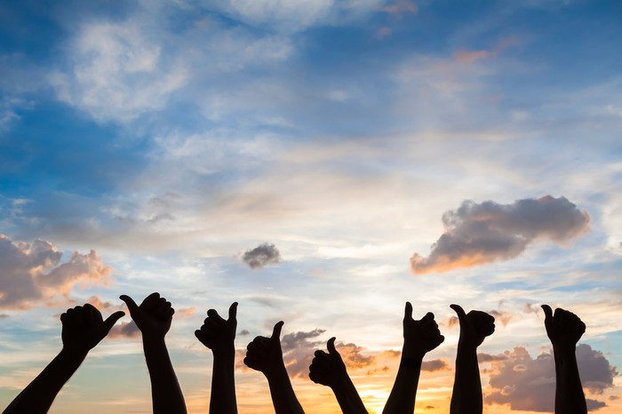 Silhouettes of eight outstretched hands giving thumbs-up signs against a colorful sunset.