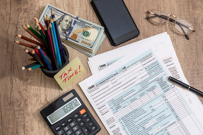 Tax forms, calculator, money, pencils, and glasses on a table.