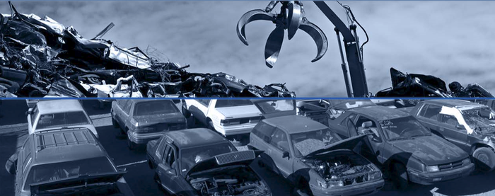Junkyard with old cars and grabber-crane to pick them up.
