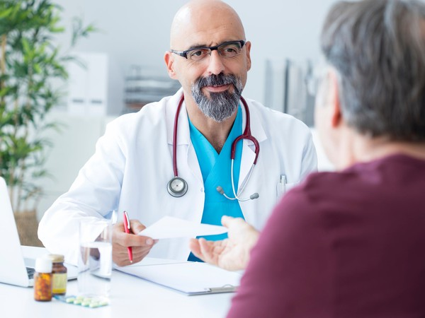 male doctor talking to gray-haired patient_GettyImages-852090066