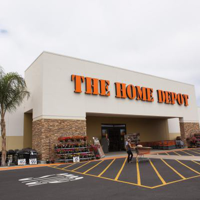 View of a Home Depot from the parking lot. A customer is pushing a cart out of the store.