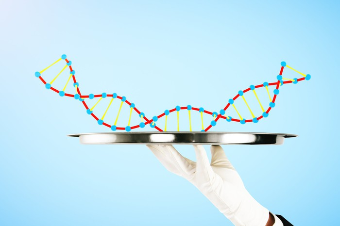 A cartoon piece of DNA being held on a silver platter by a white-gloved hand