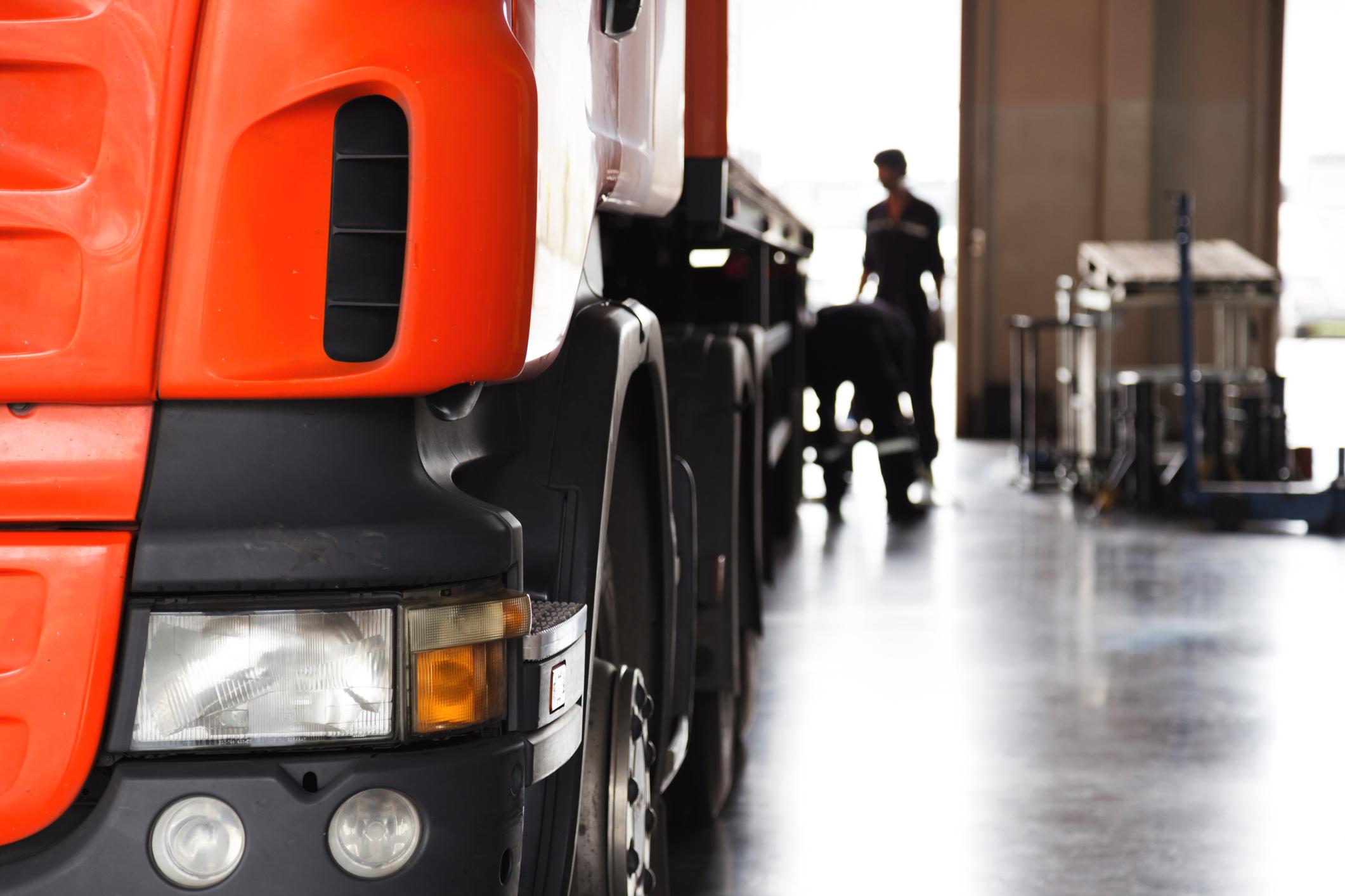 Vehicle mechanic inspecting semi-truck in large maintenance garage.