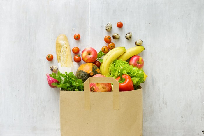 Produce spilling out of a paper bag placed flat on wooden table, seen from above.