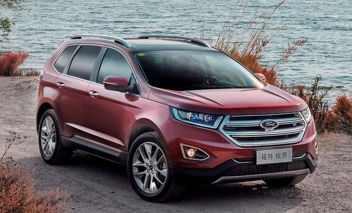 A red Ford Edge, a midsize crossover SUV, parked on a waterfront. The Edge has a Chinese-language front license plate.