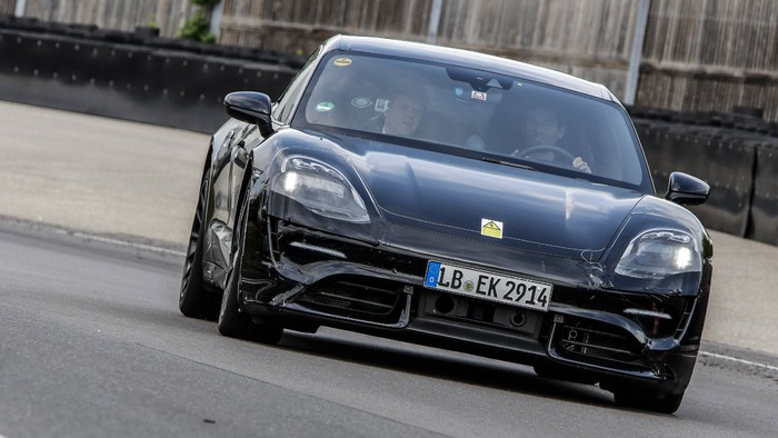 A black preproduction Porsche Taycan, an electric sports sedan, shown from the front on a test track.