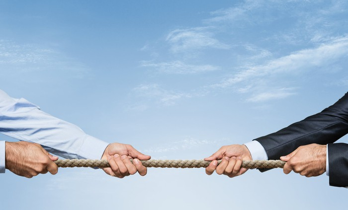The arms of two men in business attire engaged in a tug of war.
