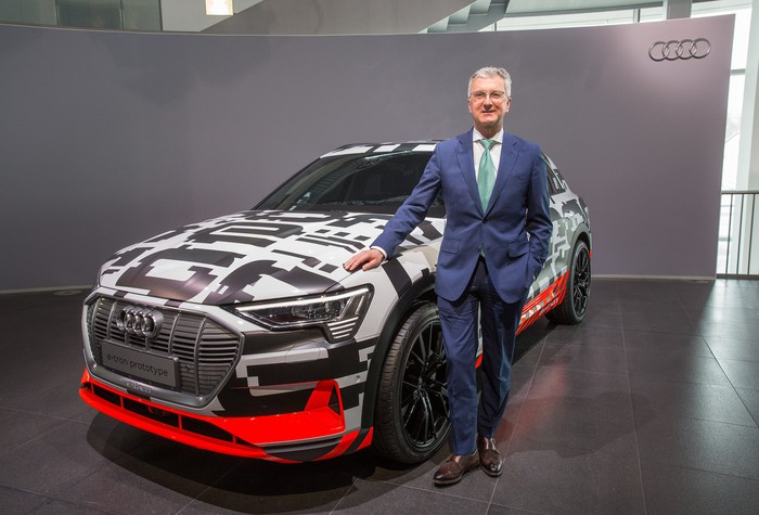 Stadler, in a blue suit, is standing next to the Audi etron quattro prototype, a midsize electric SUV wrapped in black and white camouflage.