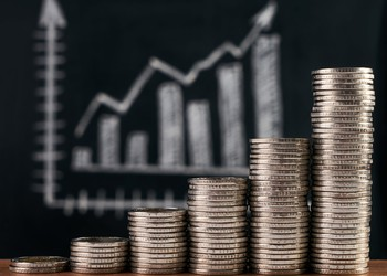 A rising stack of coins with a bar chart and an upward arrow in the background.