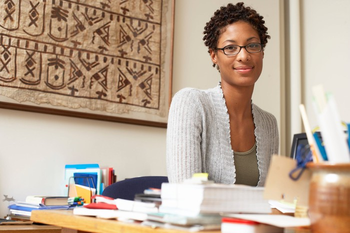 A woman sits at a table in a home office.