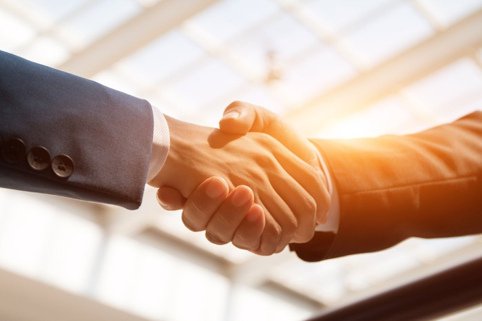 Two businessmen shaking hands, as the sun shines through an overhead window.