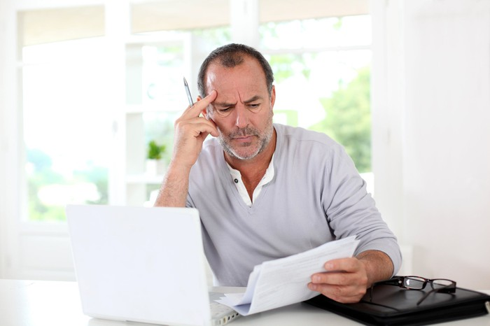 man at laptop looking confused about paper he is holding