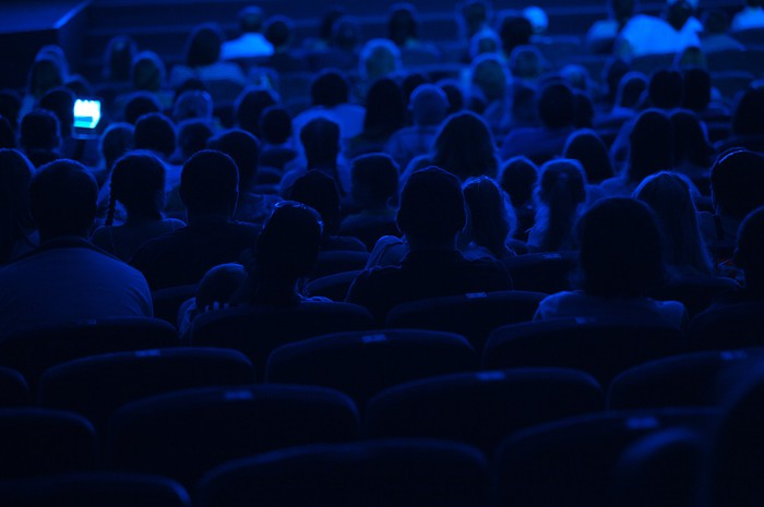 Movie-goers in darkened theater shown from behind.