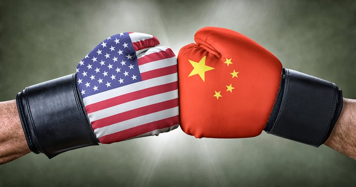 The hands of two different people wearing boxing gloves, with the US and China flags. The gloves are touching each other.