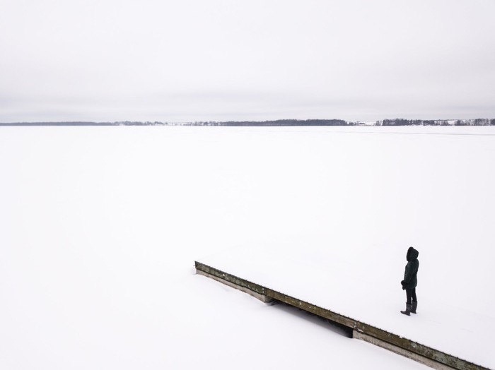 Woman in winter outerwear standing on snow-covered pier overlooking a frozen lake.