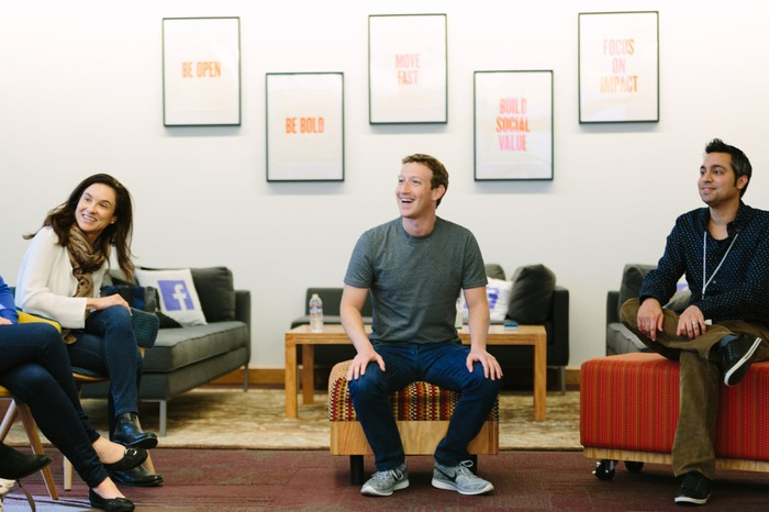 Mark Zuckerberg sitting on an ottoman smiling, with a man and a woman on either side of him