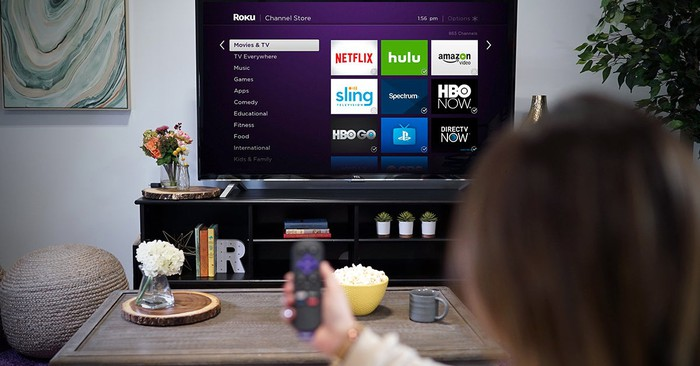A woman pointing a Roku remote control at a TV displaying the Roku Channel homepage
