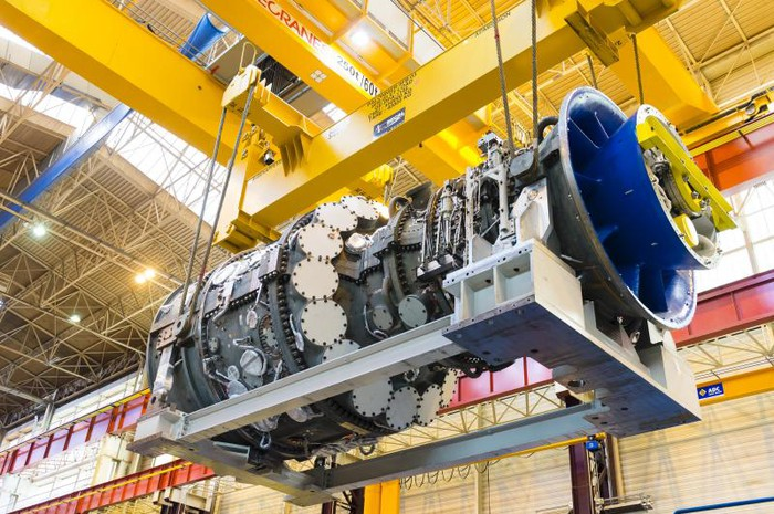 A gas turbine being moved in an indoor manufacturing facility.