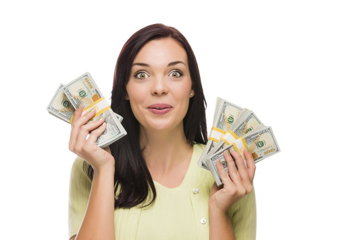 A happy-looking woman holds stacks of $100 bills.