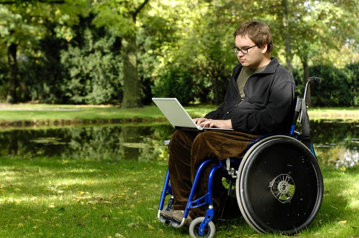 A boy with muscular dystrophy sitting in a wheel chair with a laptop.