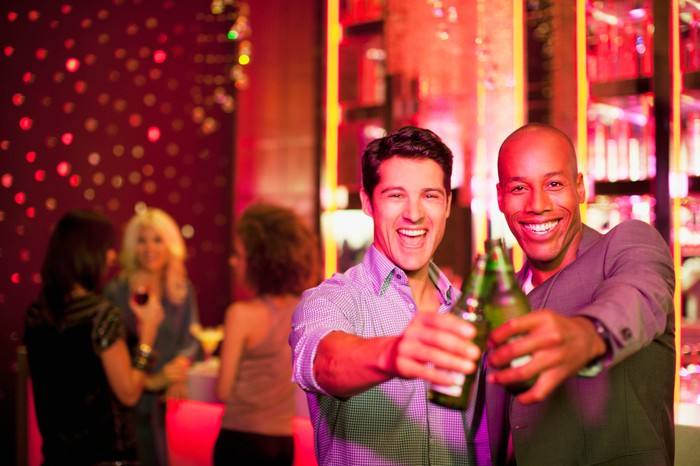 Two men holding bottled beers in a club.
