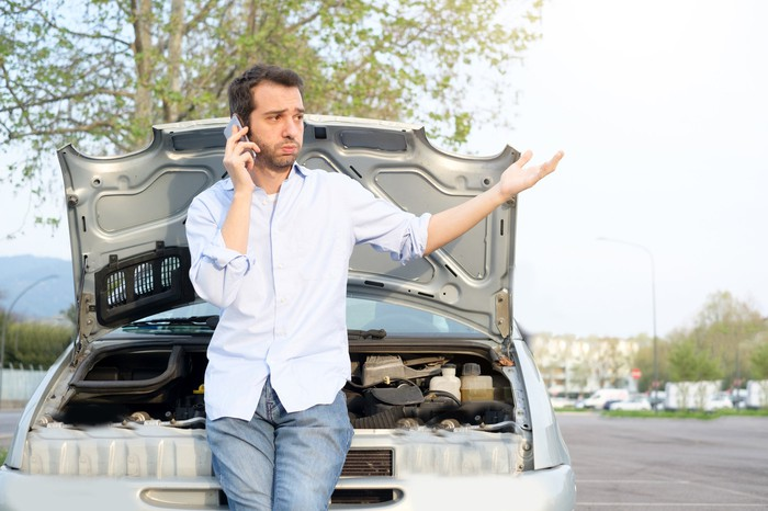 Man on the phone standing in front of a car with its hood up