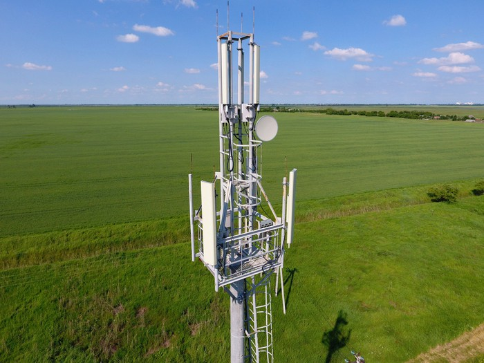 Cell tower in a large grassy field.