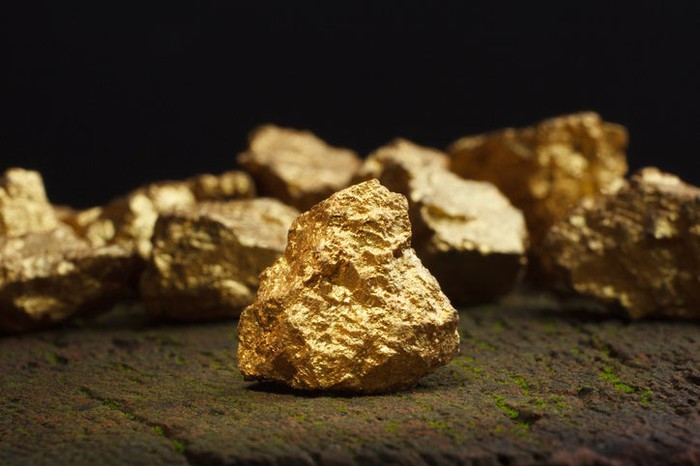 Gold nuggets sitting on the ground.