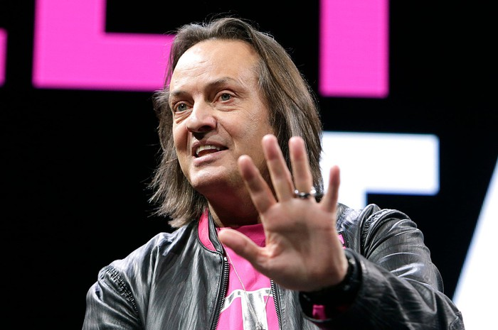 T-Mobile CEO John Legere smiling with his left hand up