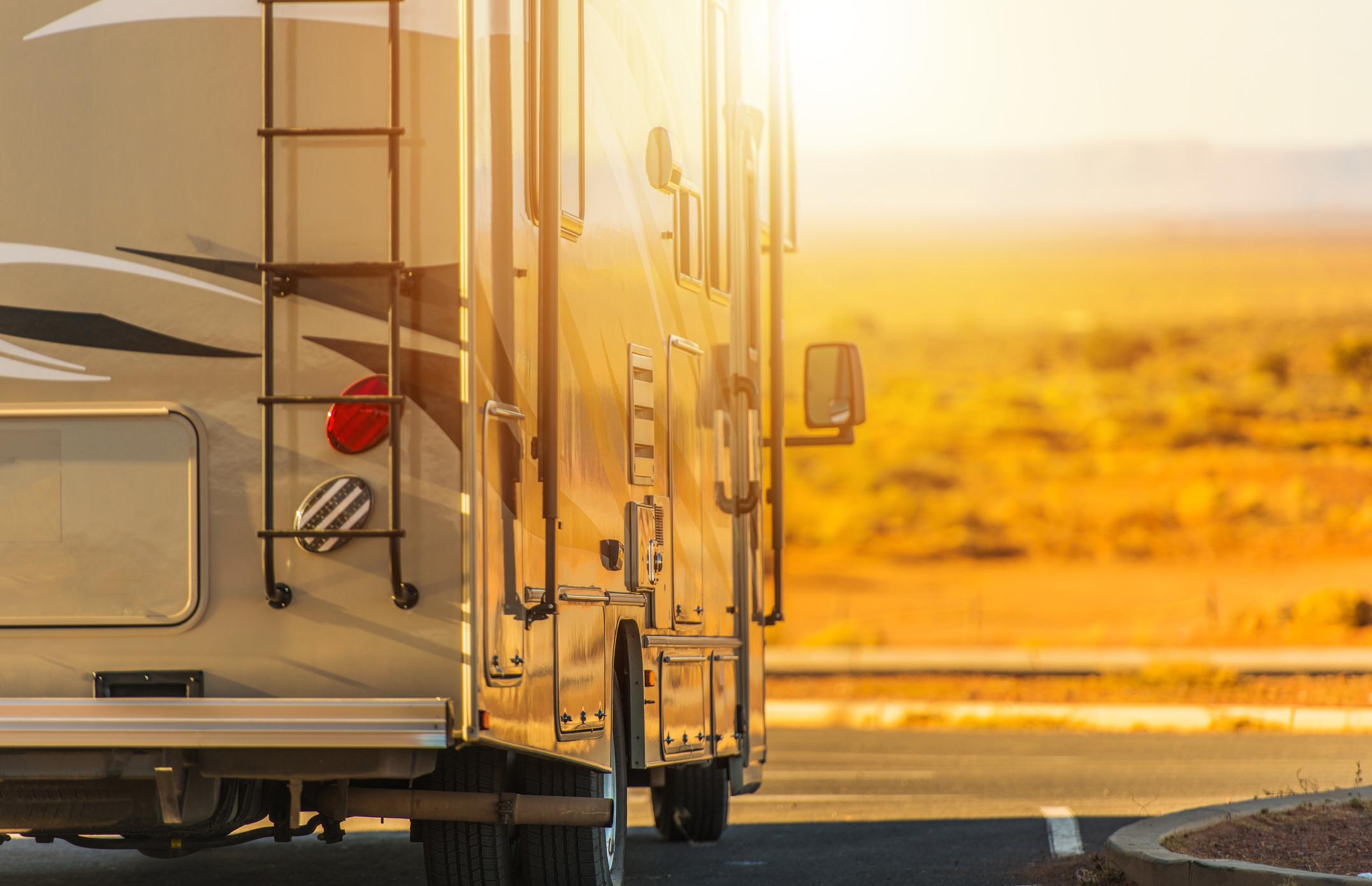 Large motorized recreational vehicle on road at dusk.