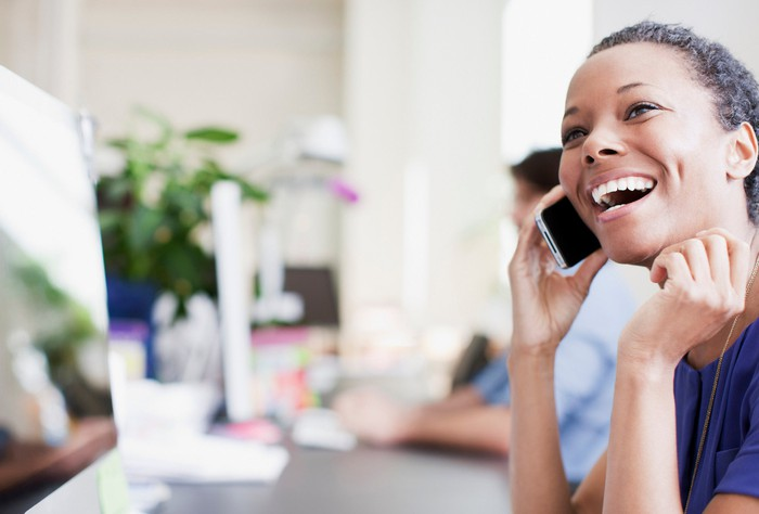 Smiling woman talking on a cell phone.