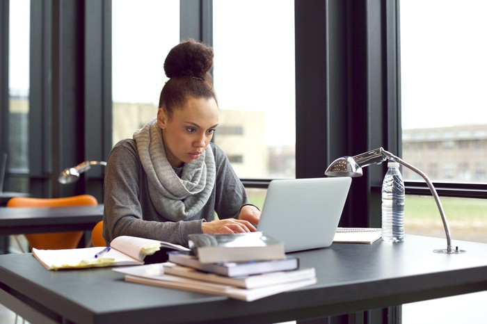 Young female at a laptop next to a pile of books and open notebook