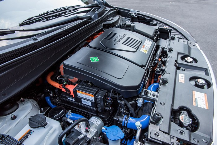 "A view under the hood of a Hyundai Tucson Fuel Cell SUV. The fuel cell ""stack"" is visible under a black cover."