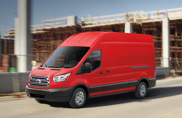 An orange Ford Transit, a commercial van that is similar in length to a large sedan, shown on a construction site.