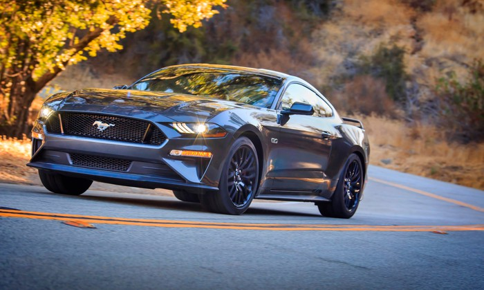 A metallic gray 2018 Ford Mustang GT fastback, shown driving on a curvy country road.