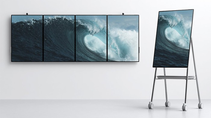 Microsoft product image of Surface Hub 2 whiteboards, mounted on walls and resting on rolling stand.