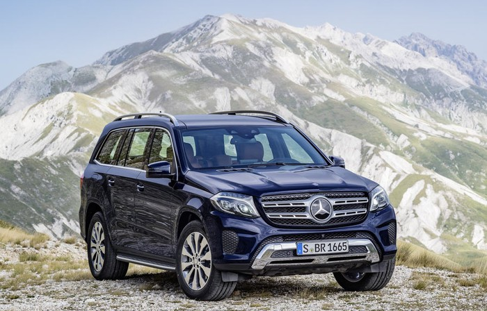 A dark blue Mercedes-Benz GLS, a large luxury crossover SUV, with mountains in the background.