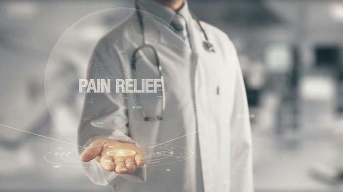 """Doctor with his hand out and the words """"pain relief"""" hovering about his open hand."""