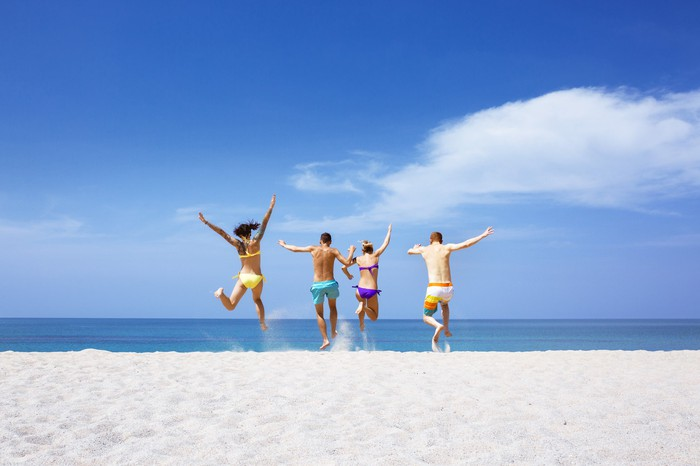 Group of people in swimsuits jumping on the beach as if celebrating