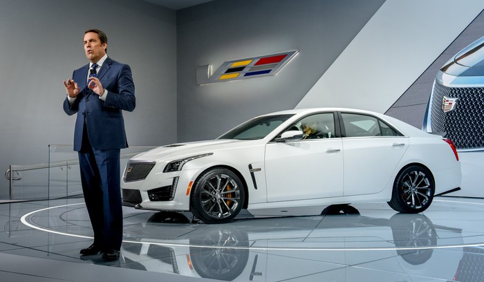 Reuss is shown standing on an auto-show stage with a while Cadillac CTS-V, a midsize high-performance luxury sedan.